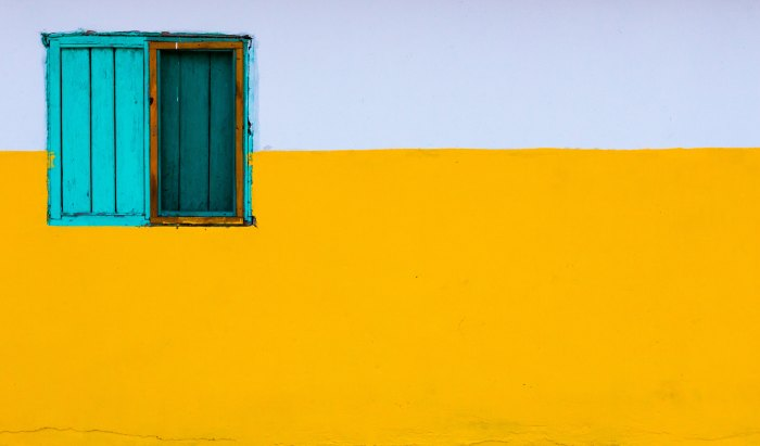 Image of a yellow and wall and a turquoise window on top left